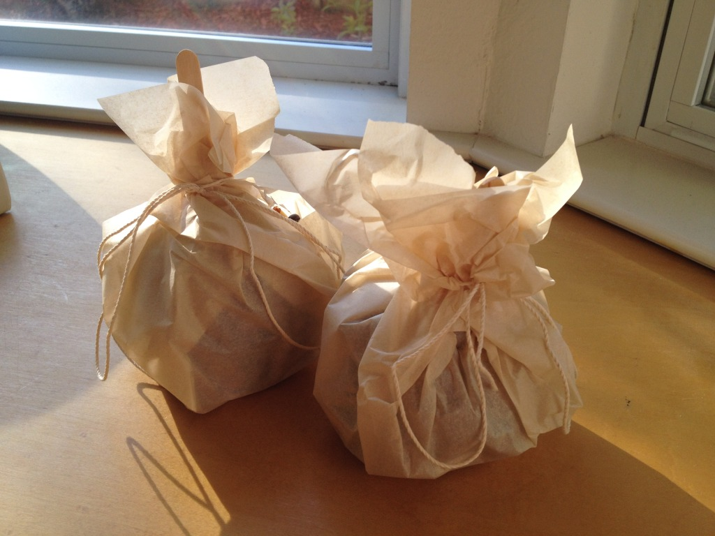 Wrap caramel apples in parchment paper and tie with string to gift